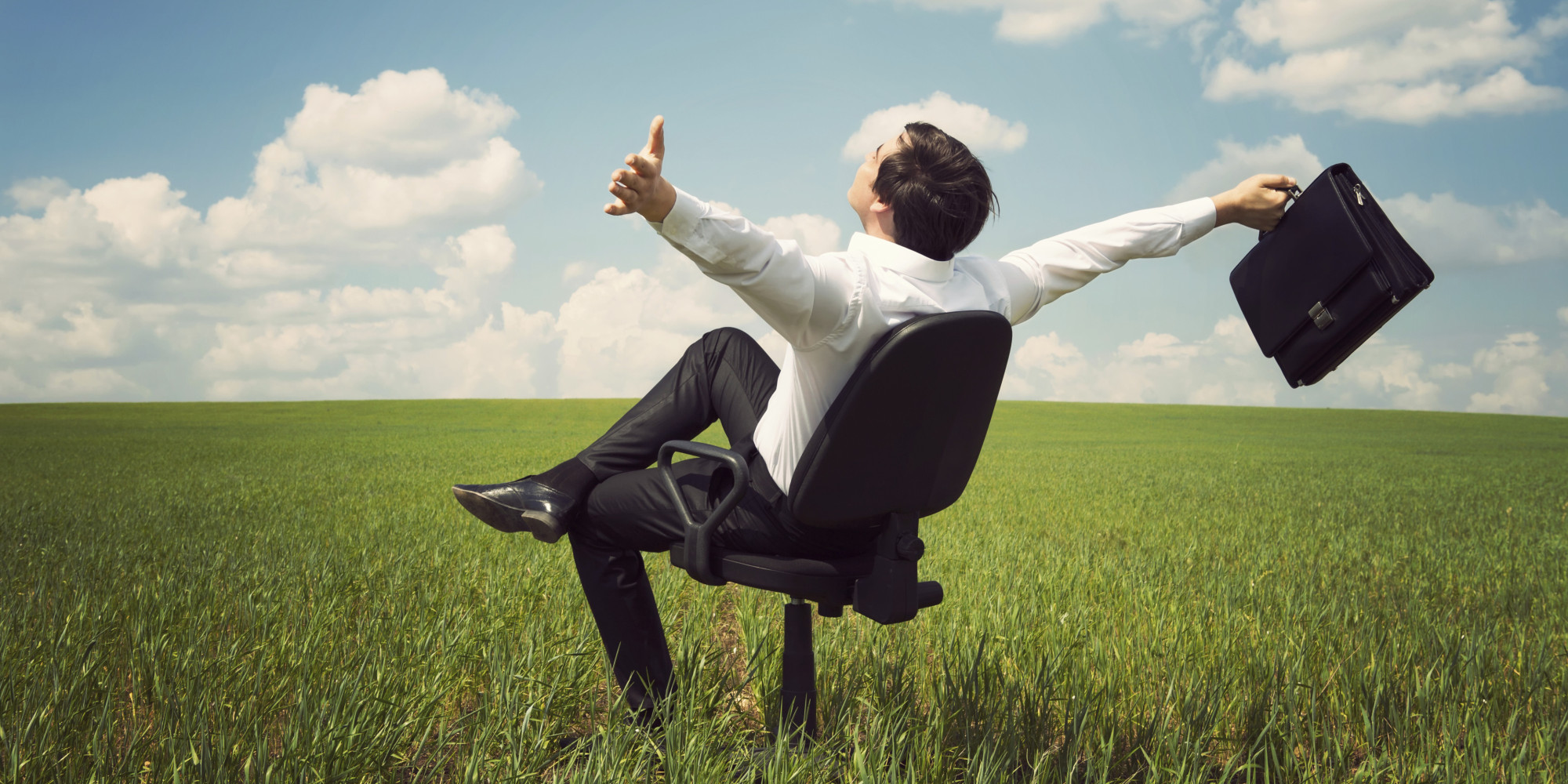 businessman in field with blue sky sitting an office chair